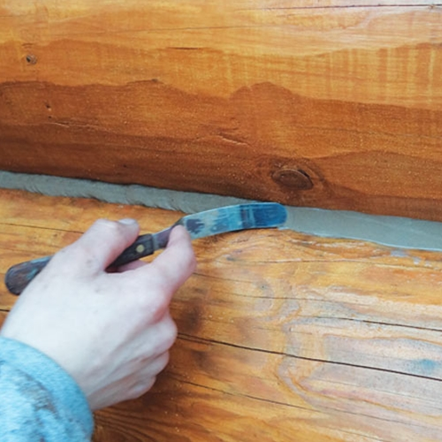 With light pressure, slide flat-bladed tool along sealant to smooth and ensure adhesion to logs